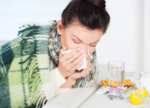 picture of woman sneezing for why you should keep your appointments when sick blog